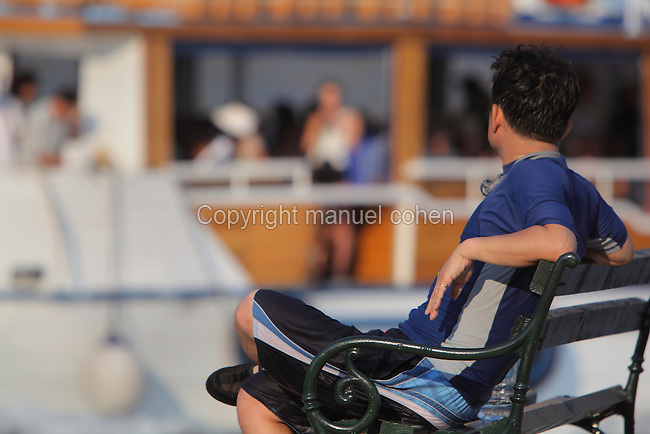 Man sitting on a bench in the Old Harbour, watching a passing boat leaving for Lokrum Island, Old Town, Dubrovnik, Croatia. The city developed as an important port in the 15th and 16th centuries and has had a multicultural history, allied to the Romans, Ostrogoths, Byzantines, Ancona, Hungary and the Ottomans. In 1979 the city was listed as a UNESCO World Heritage Site. Picture by Manuel Cohen