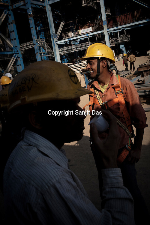 Indian labourers share a lighter moment during a tea break at the construction site of the Adani Power plant of 4620 MW capacity in Mundra port industrial city of Gujarat, India. Indian power companies have handed out dozens of major contracts to Chinese firms since 2008. Adani Power Ltd have built elaborate Chinatowns to accommodate Chinese workers, complete with Chinese chefs, ping pong tables and Chinese television. Chinese companies now supply equipment for about 25% of the 80,000 megawatts in new capacity.