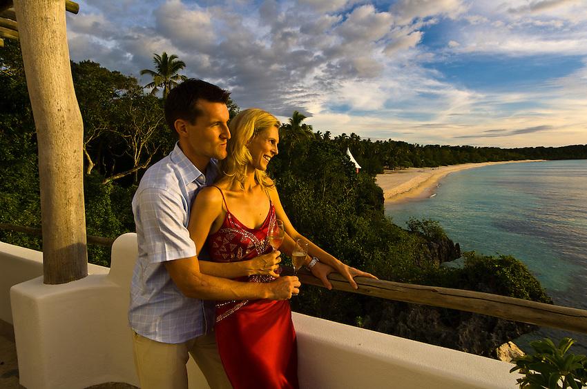 A couple on honeymoon enjoy the sunset from The Point, a villa above Vatulele Island Resort, Fiji Islands