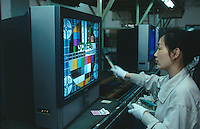 China. Province of Zhejiang. Hangzhou. Soyea is one company of the West Lake Electronics Group Co., Ltd.  Soyea produces television sets for the chinese market. A woman controls the good functionning of  electronic components in a new TV set and the quality of the screen by using a colorful tv test card. She is a worker on an assembly line. © 2004 Didier Ruef