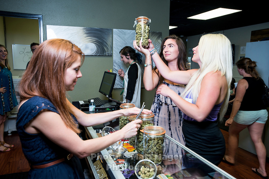 Budtender Jasmine Maimone (cq) shows marijuana to Stephanie Moore (cq, dark hair) and Samantha Campion (cq, blond hair) at a LiveGreen Cannabis store in Denver, Colorado, Monday, July 21, 2014. <br /> <br /> Photo by Matt Nager