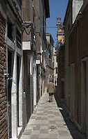 Man walking through Venetian alley,Venice, Italy, May 2007.