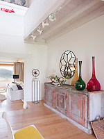 A large circular mirror hangs on the wall behind, and a trio of oversized coloured glass vases sit on, a distressed wooden sideboard in the entrance hall