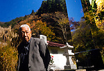 Yoshifumi Yamada, 84, chairman of Lake Shouji Touism Association, walks through a cemetery in which the remains of unidentifiable suicide victims are interred   near Aokigahara Jukai, better known as the Mt. Fuji suicide forest, which is located at the base of Japan's famed mountain west of Tokyo, Japan on 03 Nov. 2009. The local community built a hall, the white building reflected in the background of the photo, especially for the suicide victims to be interred.