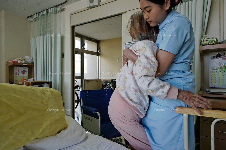 "Japan has too many elderly and not enough young people to staff all the nursing homes and care units in hospitals, so they have a program that brings in thousands of Philipino and Indonesian workers just for that purpose.  The two women in these photographs helping the elderly at the permanent care unit are:.KUSUMAWATI (Last Name), Ratri.NURZAKIHA (Last Name), Nunur .This is the hospital that has the robotic legs and the immigrant workers are being brought in for the same reason the robotics people are working on solutions for lonely elderly.  All of these robotics folks developing robots for elderly talk about studies showing that more and more elderly are isolated and have no one to relate to... In 2009 it was 19 percent of the elderly population of Japan.  They have a word for it:  ""Kodokushi"" or ""lonely death.""."