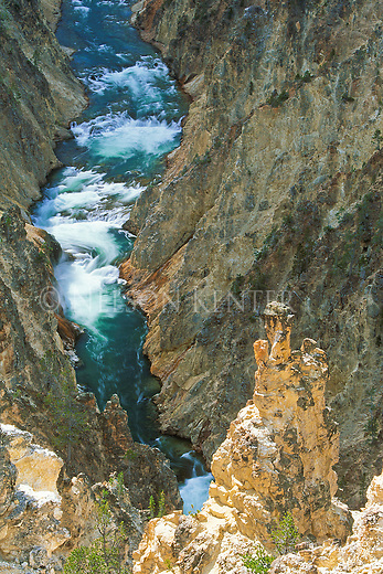The Yellowstone River flows through steep rocky cliffs in the Grand Canyon of the Yellowstone