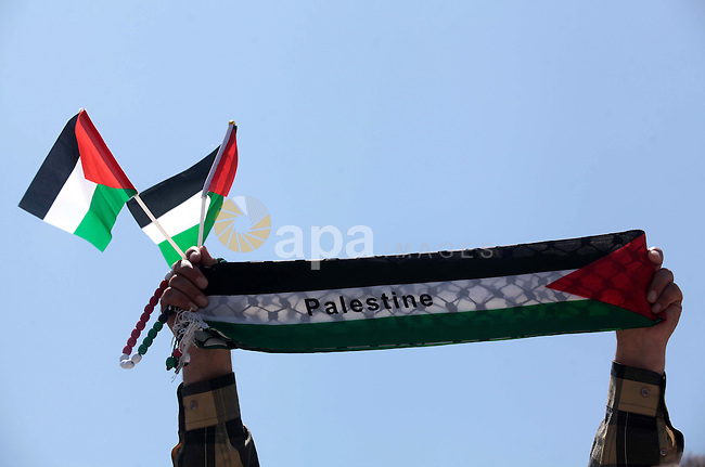 A Palestinian man holds a Palestine flag during a demonstration to calling for an end in the political division and the national reconciliation in Gaza city, on April 22, 2014. A delegation representing the PLO is expected to arrive in Gaza on Tuesday evening for reconciliation meetings with Hamas, a Fatah spokesman said. Photo by Ashraf Amra