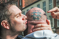 A protestor kisses the head of a man with an 'England' tattoo at an anti-facist demonstration. Manchester, United Kingdom, 11/10/09.