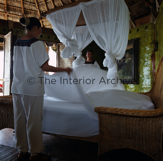 Two chambermaids making up a wicker bed in one of the hotel's guest rooms