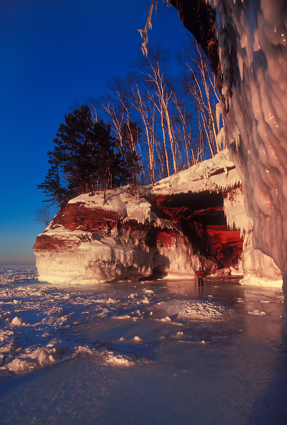 A snowshoer explores the ice-covered sea caves of Lake Superior at Squaw Point in Apostle Islands National Lakeshore near Bayfield, Wis.