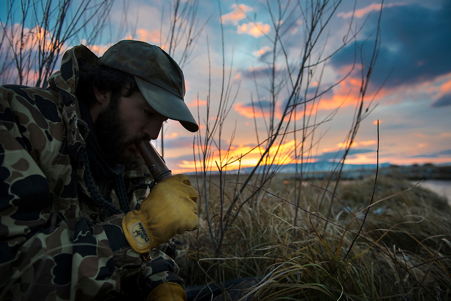 A duck hunter calls as dawn break in western Montana.