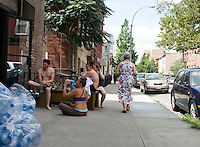 Yoga students resting on the sidewalk. Williamsburg Brooklyn, New York.