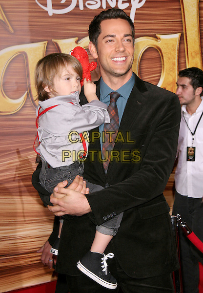 "GUEST & ZACHARY LEVI.Disney Premiere of ""Tangled"" held at El Capitan Theatre in Hollywood, California, USA..November 14th, 2010.half length black jacket holding carrying kid child.CAP/RKE/DVS.©DVS/RockinExposures/Capital Pictures."