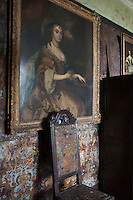 Hand-painted embossed leather lines the walls of the red four-poster bedroom graced with a collection of gilt-framed portraits