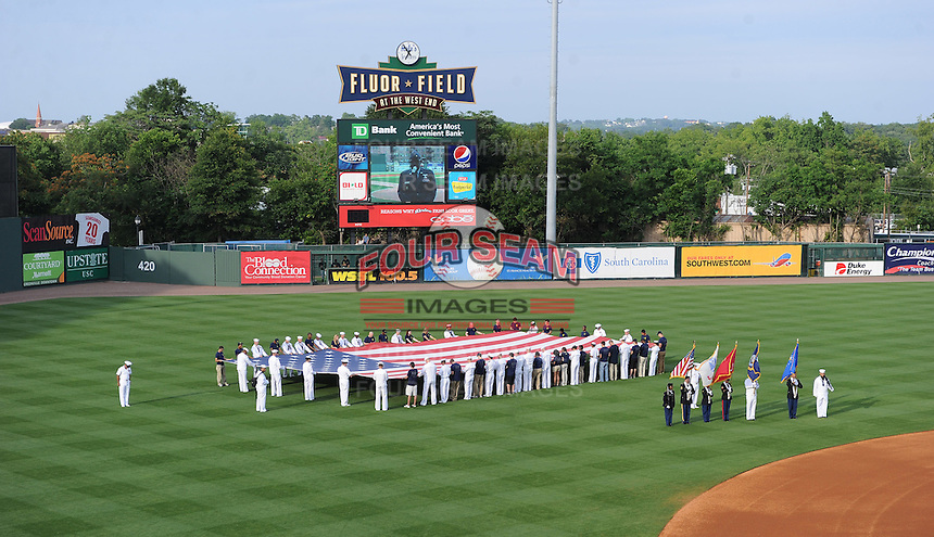 A large US flag us unfurled on the field during Military Apperciation Day prior to a game between the West Virginia Powerand the Greenville Drive on May 19, 2012, at Fluor Field at the West End in Greenville, South Carolina. (Tom Priddy/Four Seam Images)