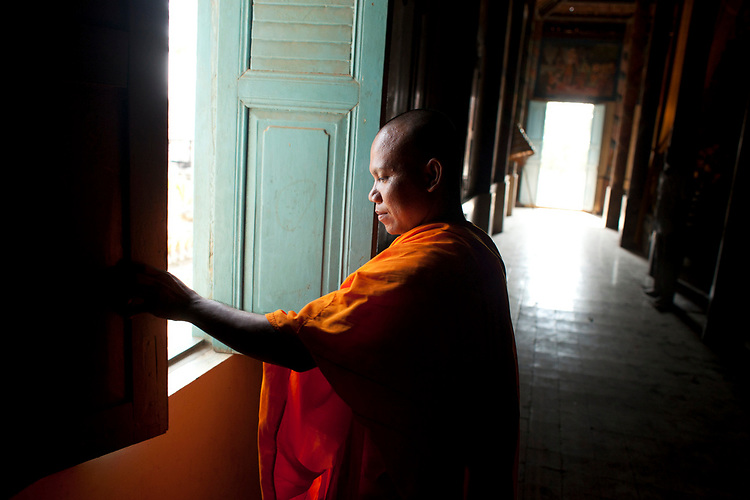 A monk closes a window in a small village temple outside of Phnom Penh, Cambodia. <br /> <br /> Photos &copy; Dennis Drenner 2013.