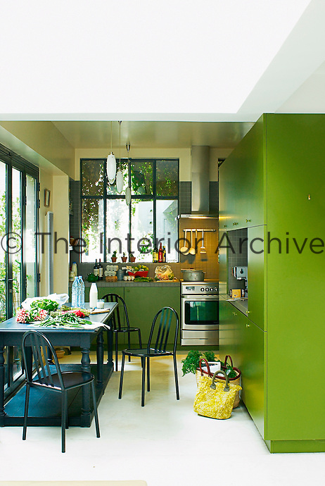 The  contemporary kitchen is painted a fresh and vibrant green