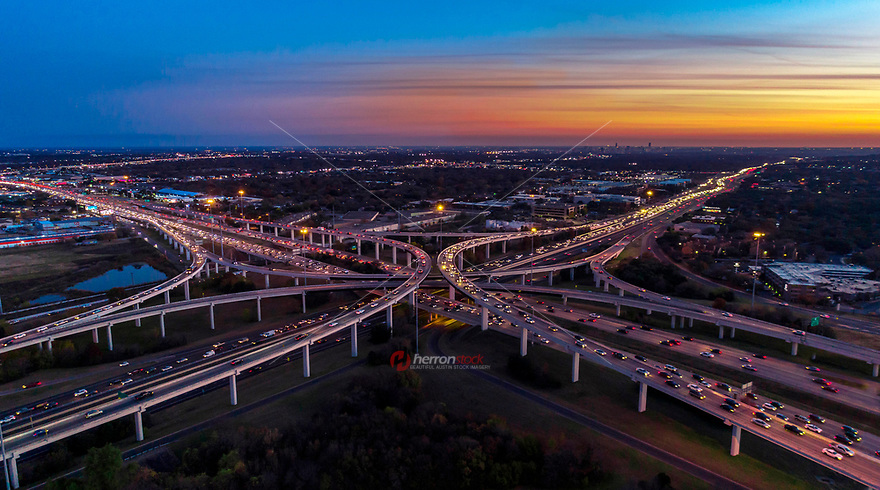 Aerial Flight View during beautiful sunset of freeway rush hour traffic on Highway 183 N and MoPac Loop 1 spaghetti highway interchange with bumper-to-bumper traffic on all levels.