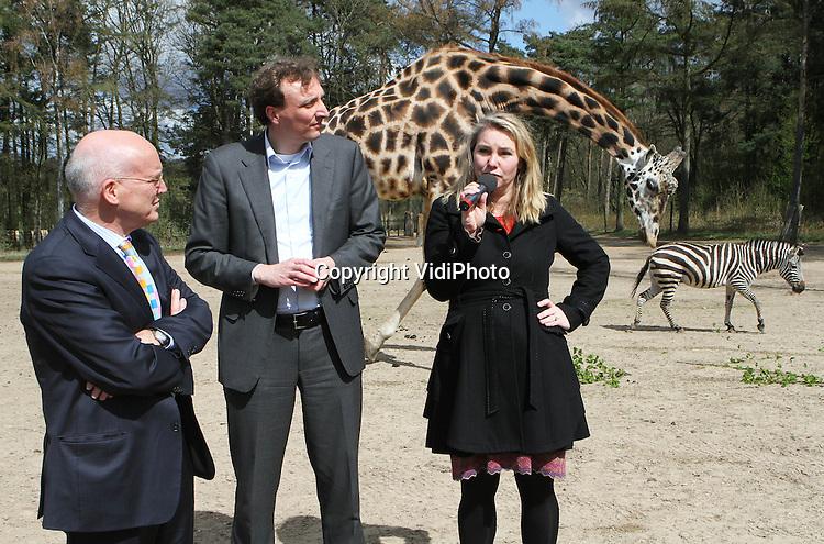 Foto: VidiPhoto..ARNHEM - Minister Schultz op safari. Na een korte safari op de savanne van Burgers' Zoo in Arnhem, kwam minister Melanie Schultz van Haegen maandag oog-in-oog te staan met enkele giraffen. De minister was maandag op werkbezoek in de regio Arnhem-Nijmegen om daar de SLIM Award uit te reiken en de Bereikbaarheidsverklaring Beter Benutten Arnhem Nijmegen te ondertekenen. Met de ondertekening werden de afspraken over de maatregelen voor een betere benutting van de infrastructuur in de regio bezegeld. Met het maatregelenpakket is in totaal 30 miljoen euro gemoeid. Foto: Minister Schultz houdt een toespraak op de savanne, terwijl Burgers'-directeur Alex van Hoof (m) en Jaap Modder, voorzitter van de stadsregio, aandachtig luisteren..