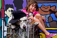 A golden retriver dog with sunglasses and a hat sitting in a shopping cart with a small girl