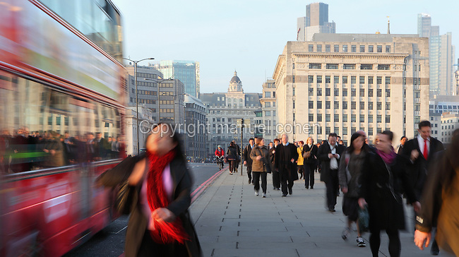 Atmospheric street scene with pedestrians and bus passing at rush hour on the London Bridge, London, England. Picture by Manuel Cohen