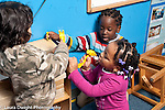 Education prechool 3- 4 year olds group of two girls and a boy playing game hammering on storage unit in block area