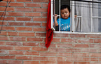 SOACHA, COLOMBIA - APRIL 15: A child looks out from a window as the local government workers deliver food to the community during the mandatory preventive quarantine to prevent the spread of the new coronavirus in Soacha Colombia on April 15, 2020. Soacha's mayor visited the slums of the town handing out baskets of food to help families in difficult financial times due to Covid-19 pandemic. (Photo by Leonardo Munoz/VIEWpress via Getty Images)