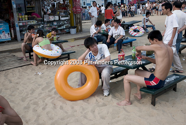 SHENZHEN, CHINA OCTOBER 2: Chinese holidaymakers eat at a beach restaurant at Dameisha Beach Park on October 2, 2008 outside Shenzhen, China. Millions of Chinese took a weeklong break during the National Holiday and one of the Golden weeks during the year. This is the most popular beach outside Shenzhen, and it's free. The park also has carnival rides and a statue park. Chinese people love theme parks and new ones are opening constantly. It's estimated that there's about 2400 theme parks in the country. Many of the most popular parks are located around Shenzhen and over the border in Hong Kong. (Photo by Per-Anders Pettersson)...