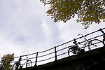 Bikes on a bridge in downtown Amsterdam, the Netherlands, framed by yellow autumn colours.