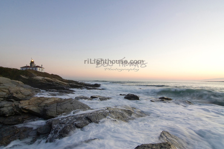 Waves lap onto the rocky shoreline by the Beavertail Lighthouse.