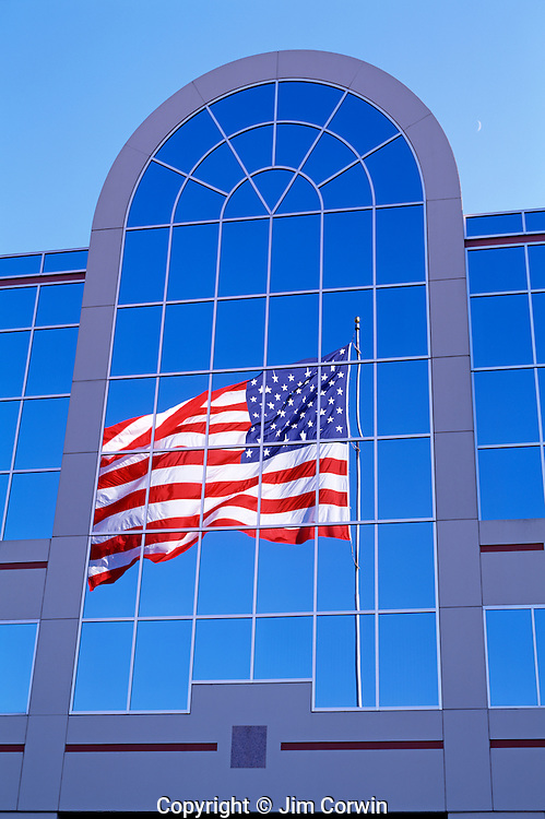 American Flag, Stars and Stripes, waving in the wind with blue sky, sunset light, with flag reflected in corporate building windows, Seattle, Washington USA.