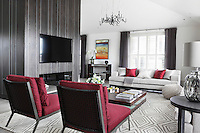A palette of red and greys has been used in the living space of this London apartment
