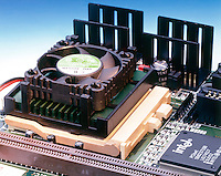 COMPUTER PROCESSOR UNIT (CPU) CHIP W/COOLING FAN<br /> Heat sinks for motherboard in background.&quot;Intel Pentium&quot; 150MHz processor in &quot;ZIF&quot; (zero insertion force) socket on motherboard.