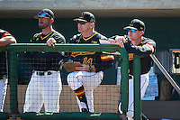 Maryland Terrapins coach Rob Vaughn, head coach John Szefc, and coach Corey Haines in the dugout during a game against the Alabama State Hornets on February 19, 2017 at Spectrum Field in Clearwater, Florida.  Maryland defeated Alabama State 9-7.  (Mike Janes/Four Seam Images)