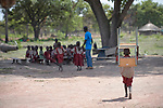 A child carries a desk toward an outdoor classroom in the Loreto Primary School in Rumbek, South Sudan. While the school, run by the Institute for the Blessed Virgin Mary--the Loreto Sisters--of Ireland, focuses on educating girls from throughout the war-torn country, it also educates children from nearby communities.