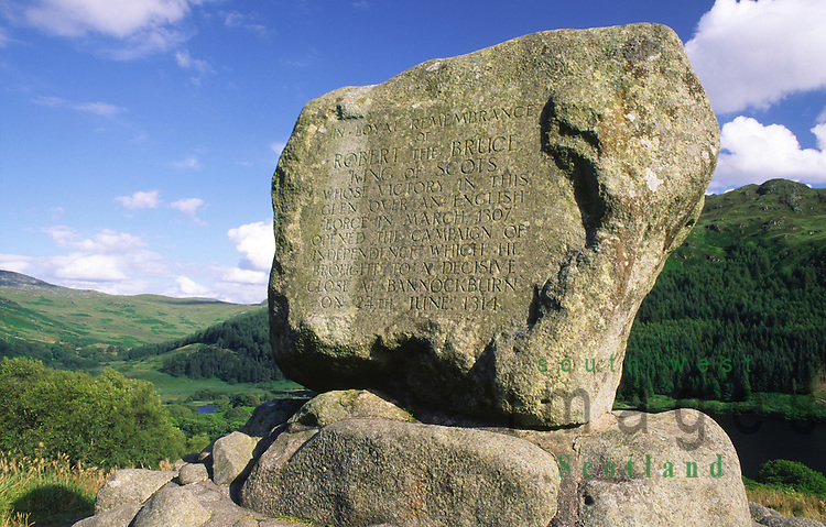 Bruces Stone commemorating Robert the Bruces victory at the Battle of the Steps of Trool in 1307 with Loch Trool and Mulldonoch behind in the Galloway Forest Park Galloway Scotland UK