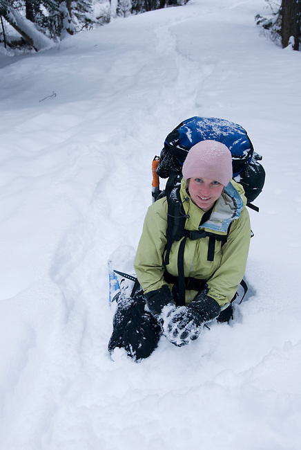 Winter scenic with young woman kneeling in snow and smiling near North St. Vrain Creek in Wild Basin, Rocky Mountain National Park, Colorado, USA, model released, (MR#91).