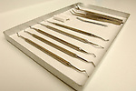 A tray of dental equipment including dental picks, scrapers and an angled mirror. Royalty Free