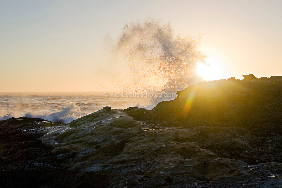 A large wave crashes over rocks along the California Coast at sunset.