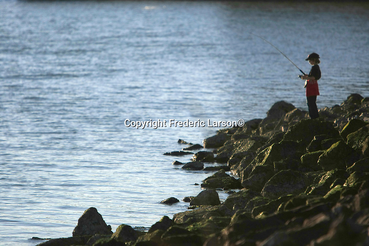 A young boy finds a great spot to fish off of the box in Richmond, California.
