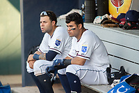 Northwest Arkansas Naturals infielders Emmanuel Rivera (26) (left) and Gabriel Cancel (18) sit in the dugout during a Texas League game between the Northwest Arkansas Naturals and the Arkansas Travelers on May 30, 2019 at Arvest Ballpark in Springdale, Arkansas. (Jason Ivester/Four Seam Images)