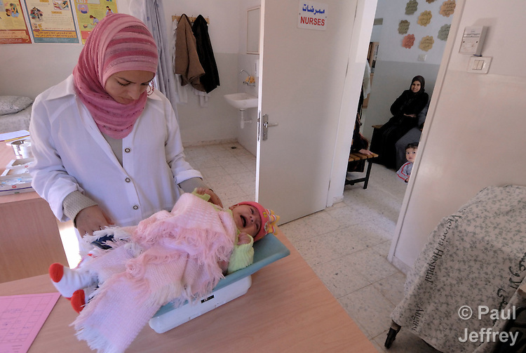 A nurse weighs a baby in a clinic, sponsored by the ACT Alliance, in the Palestinian village of Shuqba, in the West Bank.