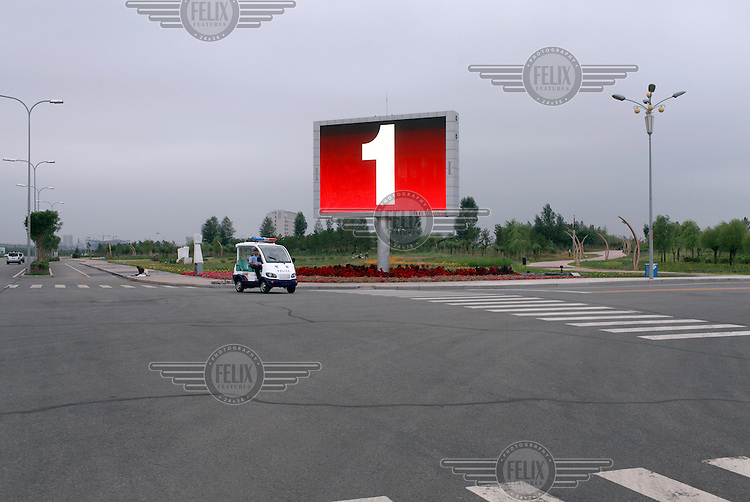 A small police buggy drives past a huge outdoor display screen while patrolling the otherwise empty streets of Kangbashi New District. With an investment of over USD 161 billion from the local government and revenue from the region's rich coal deposits, enough buildings have risen on the site of an old desert village to hold at least 300,000 residents, complete with ultra modern facilities and grand plazas. The district, however, has an occupation rate of less than 10% and has been dubbed the 'Ghost City'. Kangbashi epitomizes China's real estate bubble and by 2011 the real estate prices in Ordos had dropped by over 70%.