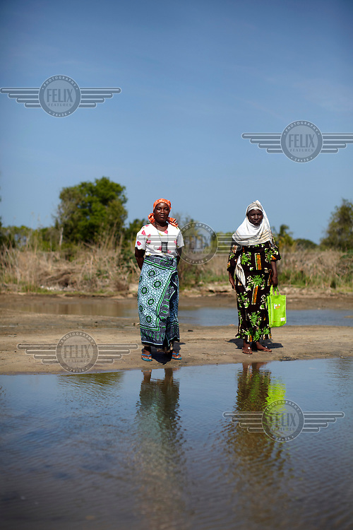 Halima Rashadi Matola and Amena Shamadi stand beside the Mpiji river. During the rainy season the river is impassable and villagers cannot access the hospital on the other side.