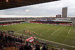 The two teams walking on to the pitch at the Alexandra Stadium on Gresty Road, Crewe, the home of Crewe Alexandra (in red) before their home game against Leyton Orient in the SkyBet League One. The match was won by the visitors from London by 2-1 with two goals on debut by Chris Dagnall, sending Orient to the top of the league. The match was watched by 4830 spectators.