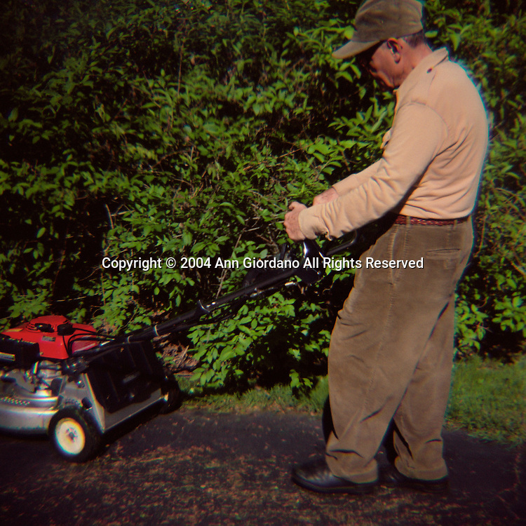 Retired man pushing lawnmower from driveway to grass