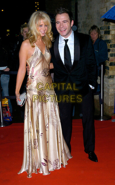 GILLIAN WALSH & SHANE FILAN .Arrivals - Emeralds & Ivy Ball, The Roundhouse, .London, England, December 1st 2006..full length married husband wife gold patterned print dress.CAP/CAN.©Can Nguyen/Capital Pictures