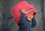 A boy carries plastic basins on his head in the Zaatari Refugee Camp, located near Mafraq, Jordan. Opened in July, 2012, the camp holds upwards of 50,000 refugees from the civil war inside Syria, but its numbers are growing. International Orthodox Christian Charities and other members of the ACT Alliance are active in the camp providing essential items and services.