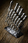 Modern steel kitchen knives set in a knife block on rustic wood background