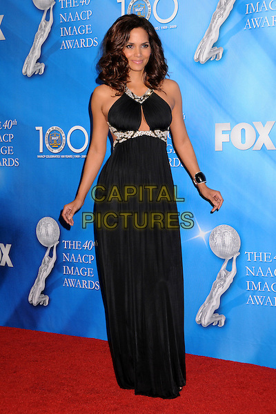 HALLE BERRY.40th Annual NAACP Image Awards - Press Room at the Shrine Auditorium, Los Angeles, California, USA..February 12th, 2009.full length long maxi black dress hands  silver beads beaded cut out away.CAP/ADM/BP.©Byron Purvis/AdMedia/Capital Pictures.